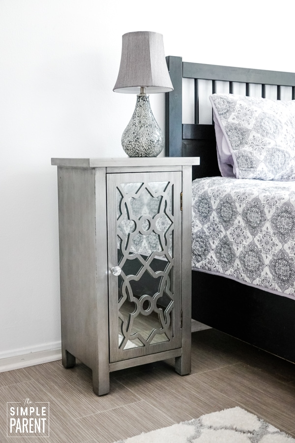 Gray nightstand with mirrored doors sitting next to a black bedframe