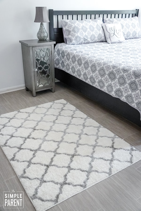 Gray and white throw rug next to a king sized bed