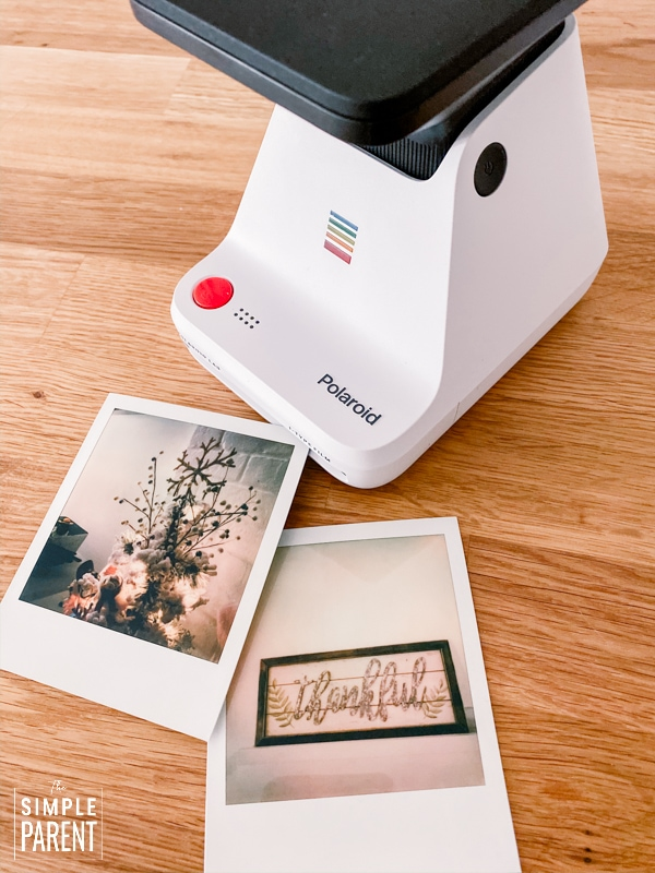 Polaroid photos sitting next to a Polaroid Lab printer