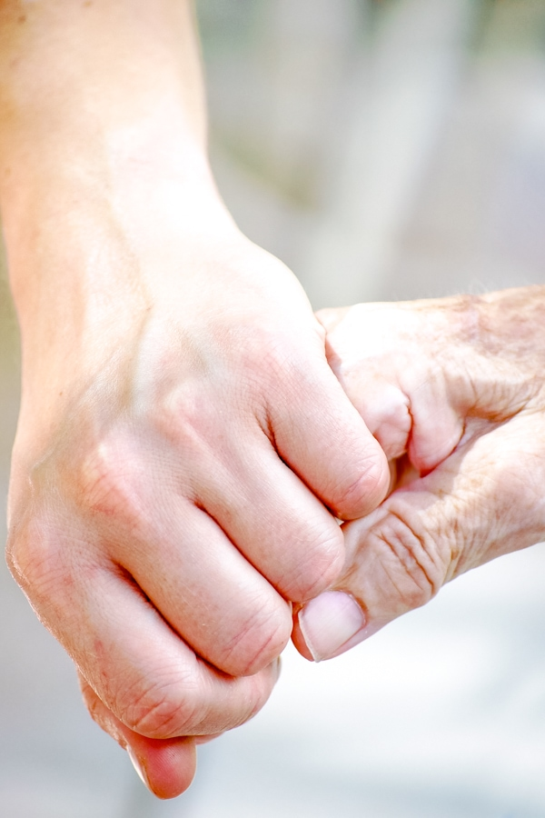 Younger person holding hands with an older adult