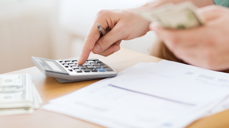 Man using calculator to count money