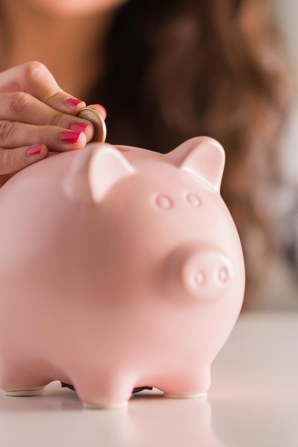 Woman putting coins into a pink piggy bank