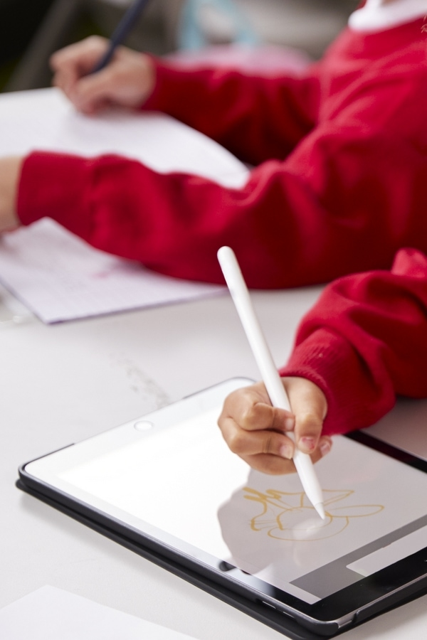 Girl wearing a red sweater while using a stylus to draw on a tablet