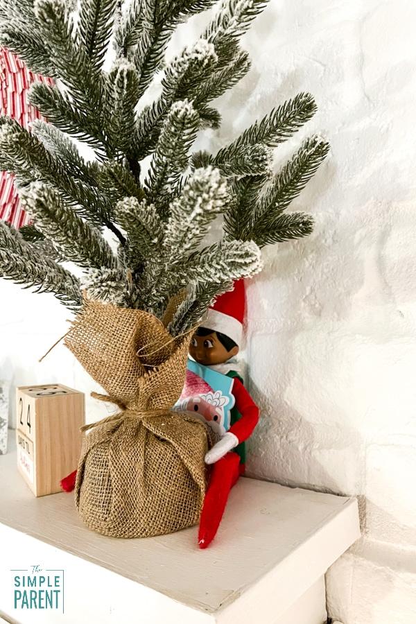 Elf on the Shelf hiding behind a miniature Christmas tree