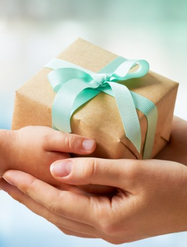Woman and child's hand holding a brown gift box with a mint green ribbon