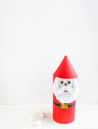 Finished paper Santa Claus craft in front of a white wall