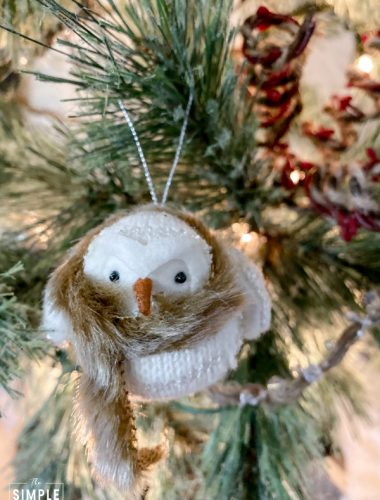 White bird ornament wearing a scarf and hanging in a green tree
