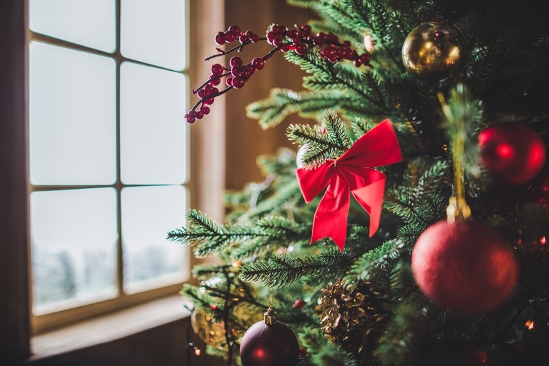 Christmas decorated with red bows and ornaments sitting by a window