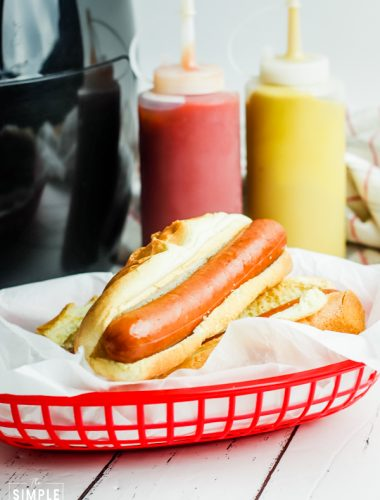 Red basket with hot dog in front of bottles of ketchup and mustard