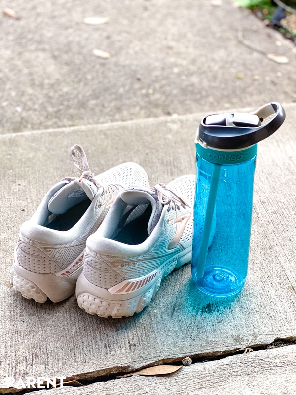 White tennis shoes and blue water bottle sitting on sidewalk