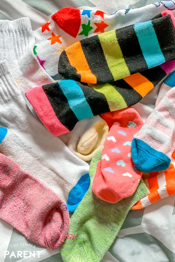 Collection of kids socks laying on a bed