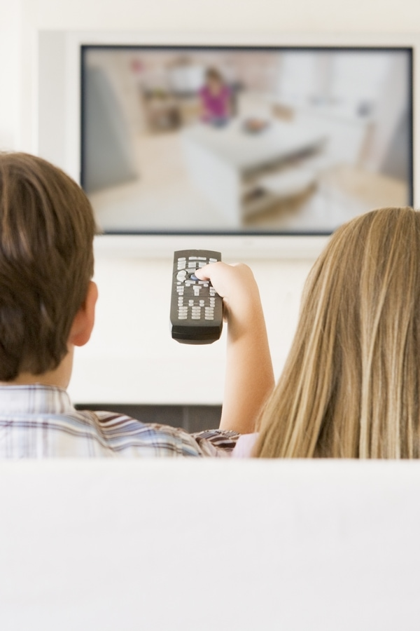 Kids sitting in front of TV with remote control