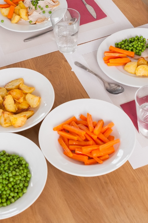 Dishes of carrots, peas, and potatoes on brown wood table