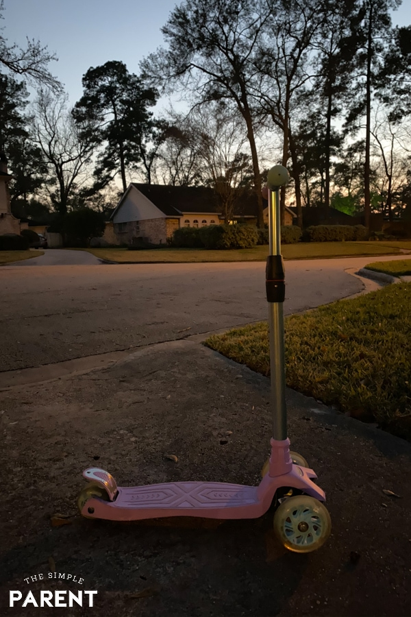 Child's scooter in a driveway at night