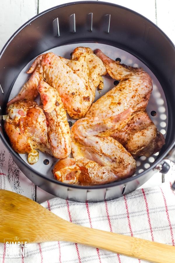 Raw chicken wings in the air fryer basket