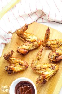 Air Fryer Chicken Wings on a cutting board with BBQ sauce