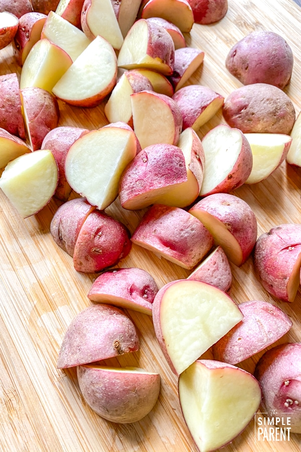 Chopped baby red potatoes on a cutting board