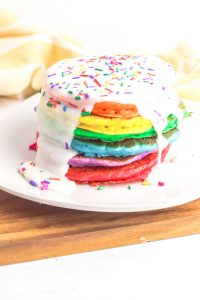 Stack of Rainbow Pancakes with white icing and sprinkles