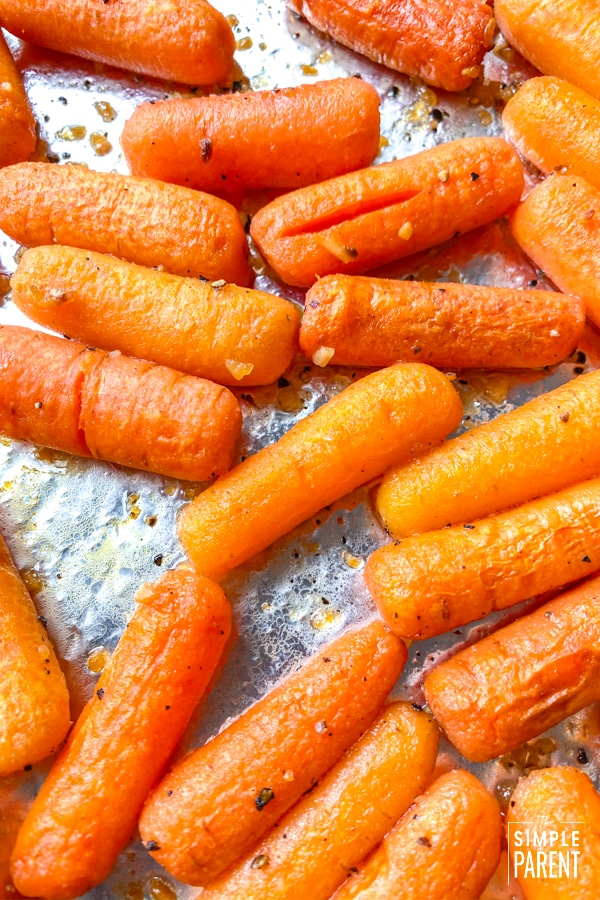 Glazed baby carrots on a baking sheet pan