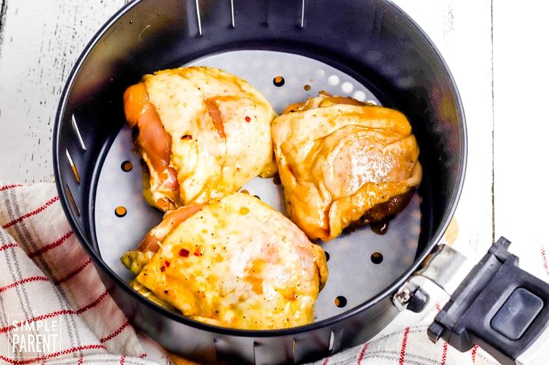 Bone-in chicken thighs in air fryer basket