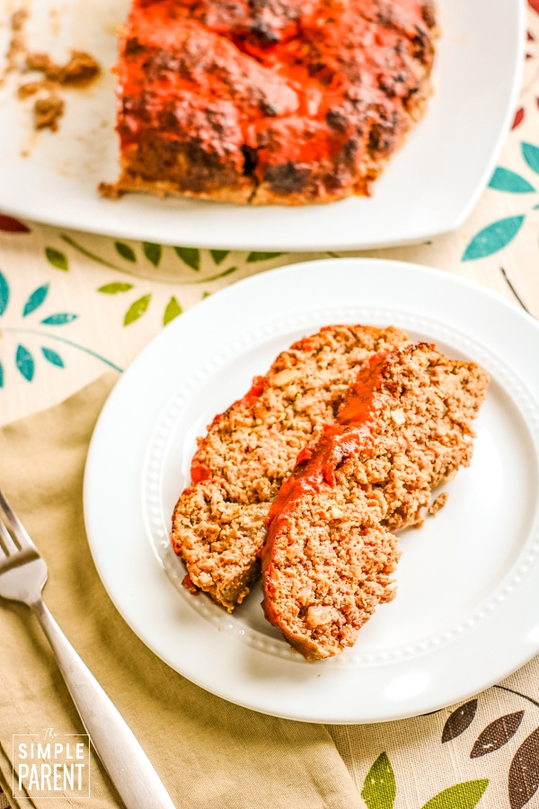 Two slices of meatloaf on a white plate with a fork