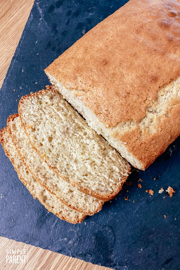 Loaf of easy banana bread sliced on a black cutting board