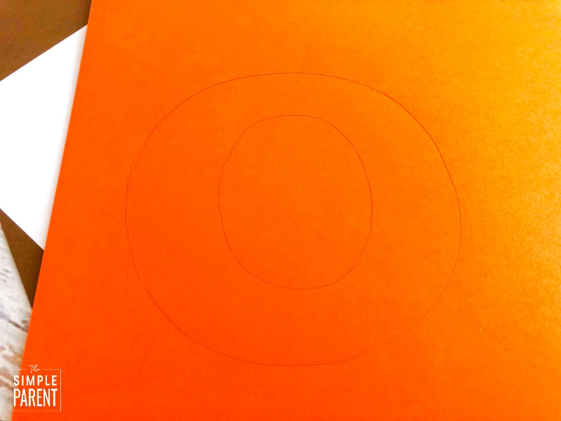 Letter O traced on orange paper