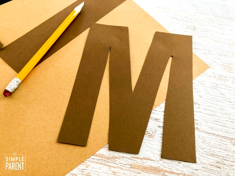Letter M cut out of brown paper