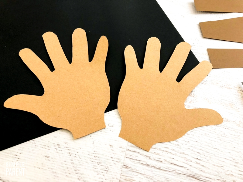 Child's handprints cut out on tan paper