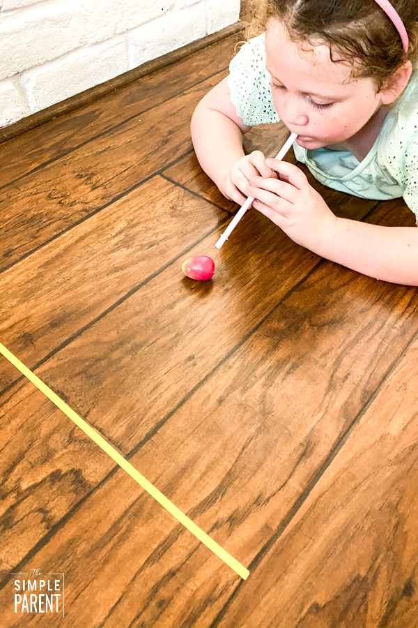 Girl playing Minute to Win It Easter Games with an egg and a straw