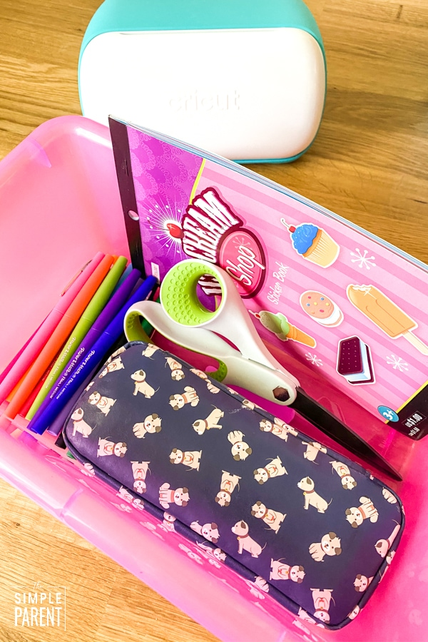 Pink plastic storage bin with school supplies in it