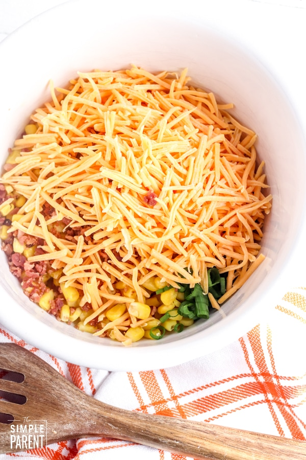 Sweet corn salad with bacon and shredded cheese in a bowl