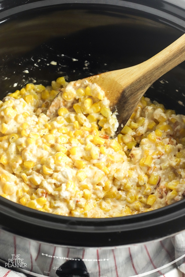 Wooden spoon mixing cheesy corn in a black Crockpot