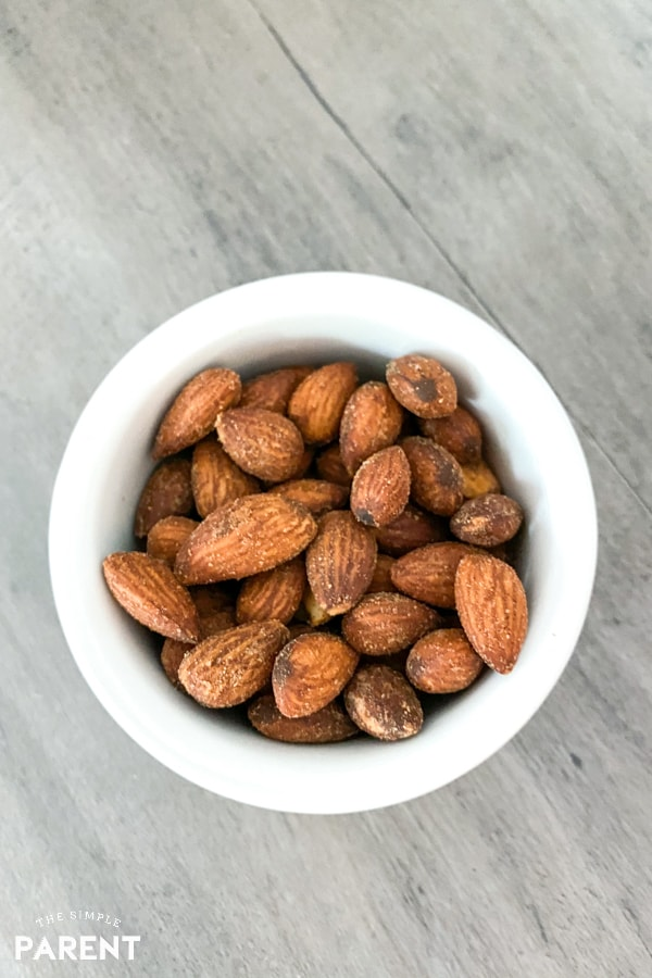 Little white bowl full of air fried almonds