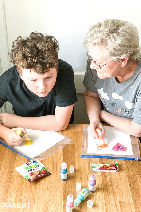 Grandmother and grandson doing a craft project with fabric paint
