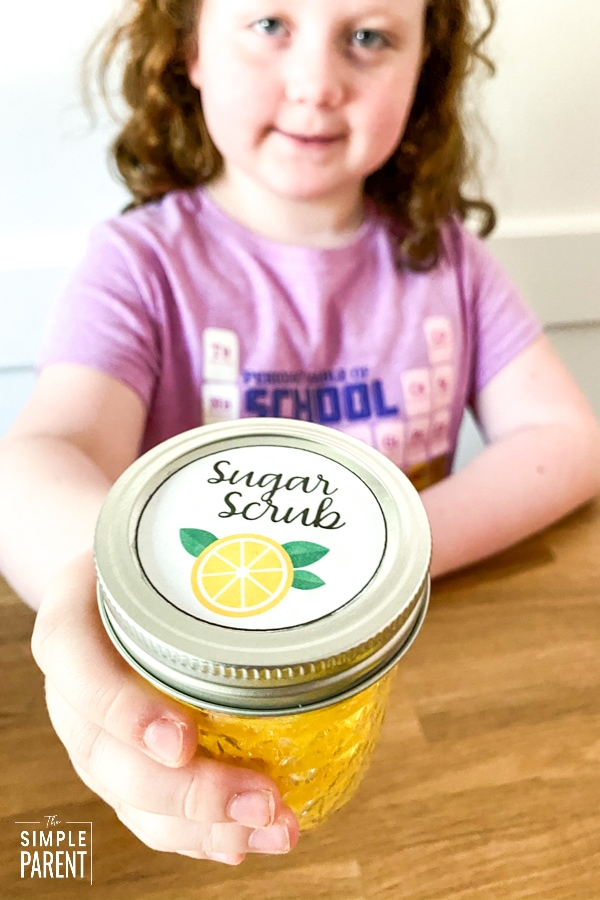 Girl holding jar of homemade lemon sugar scrub