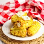 Plate of Air Fryer Corn on the Cob with a pats of butter on top