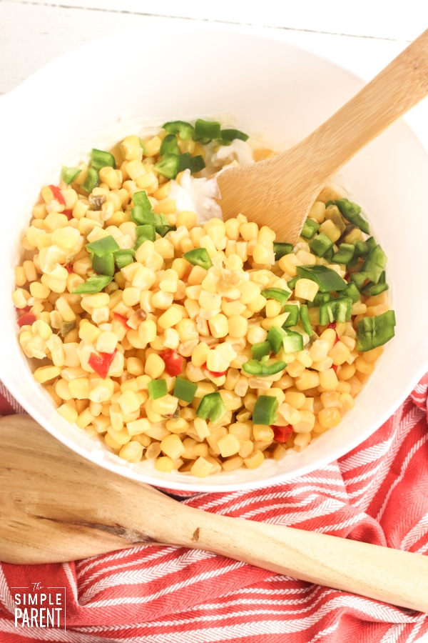 White mixing bowl with corn, tomatoes, jalapeno, and cream cheese