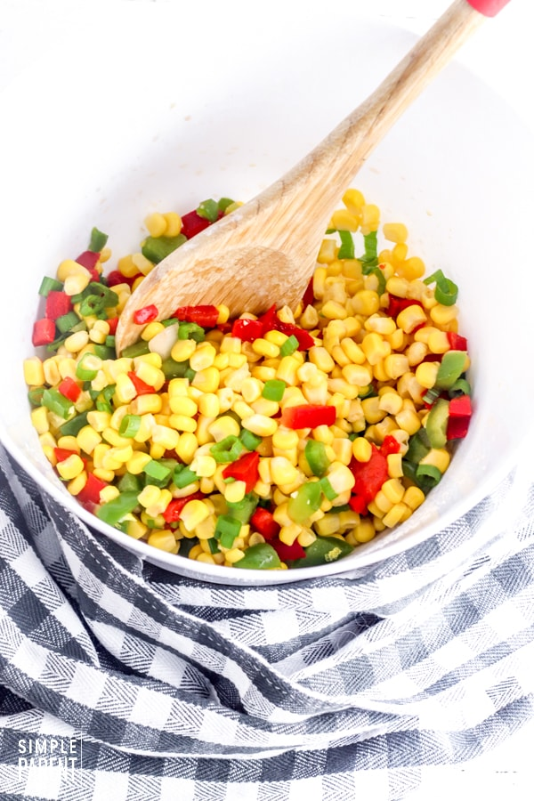 Cooked frozen corn and diced bell peppers in a mixing bowl to make cold corn salad
