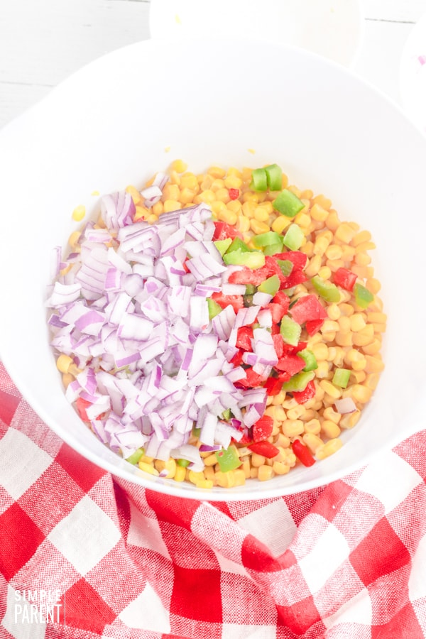 Bowl with ingredients to make Frito Corn Salad dip