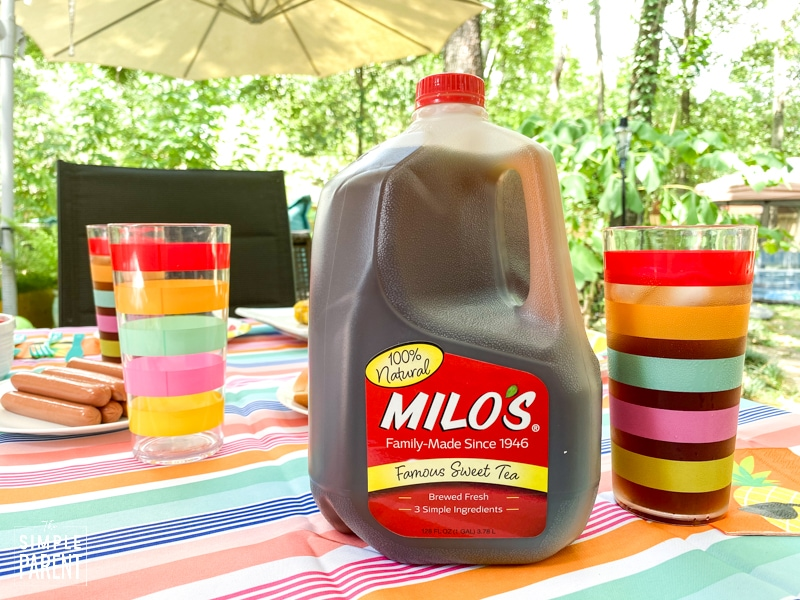 Milo's Famous Sweet Tea sitting with rainbow striped glass of iced tea