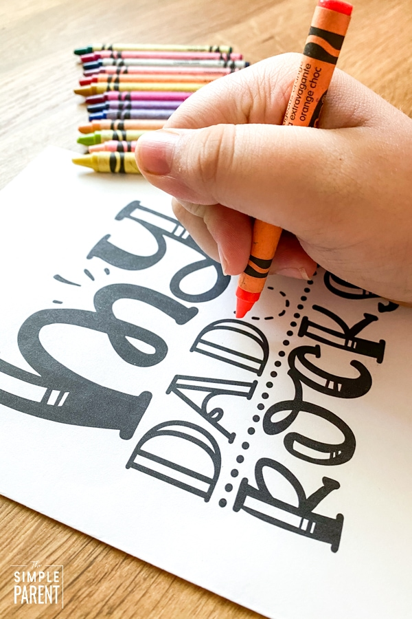 Child using crayon to color printable Father's Day card for kids