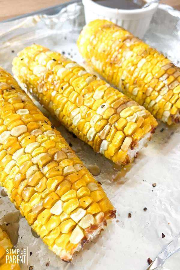 Pan of oven roasted corn with a sweet tea glaze drizzled on top