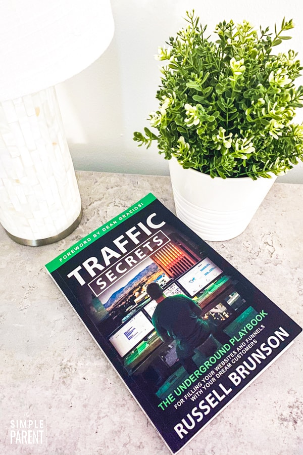 Traffic Secrets: The Underground Playbook for Filling Your Websites and Funnels with Your Dream Customers book by Russell Bronson laying on counter