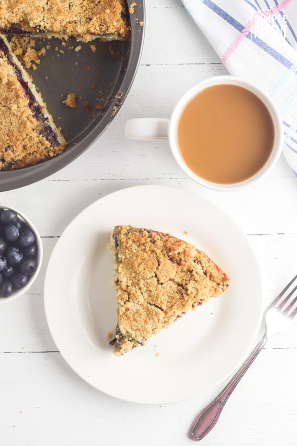 Slice of blueberry coffee cake on a white plate with a cup of coffee
