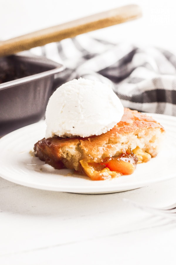 Piece of peach cobbler with vanilla ice cream