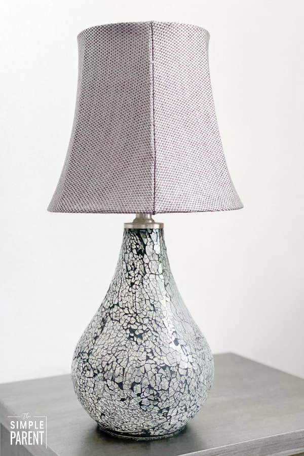 Gray glass lamp on a gray nightstand