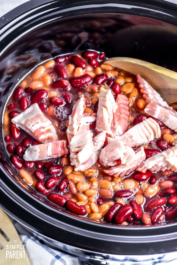 Chopped bacon on top of beans in a Crockpot