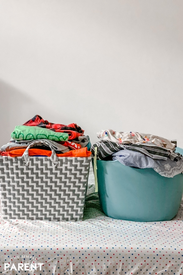 Two baskets of folded laundry on a bed