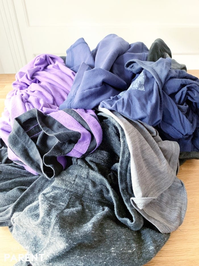 Pile of dark colored clothes on counter